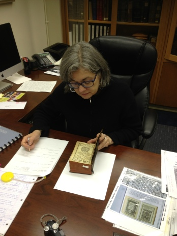 Armenian art historian Dr. Sylvie Merian examines woodcut prints in an 18th century Armenian hymnal from the Zohrab Center's collection of rare books.